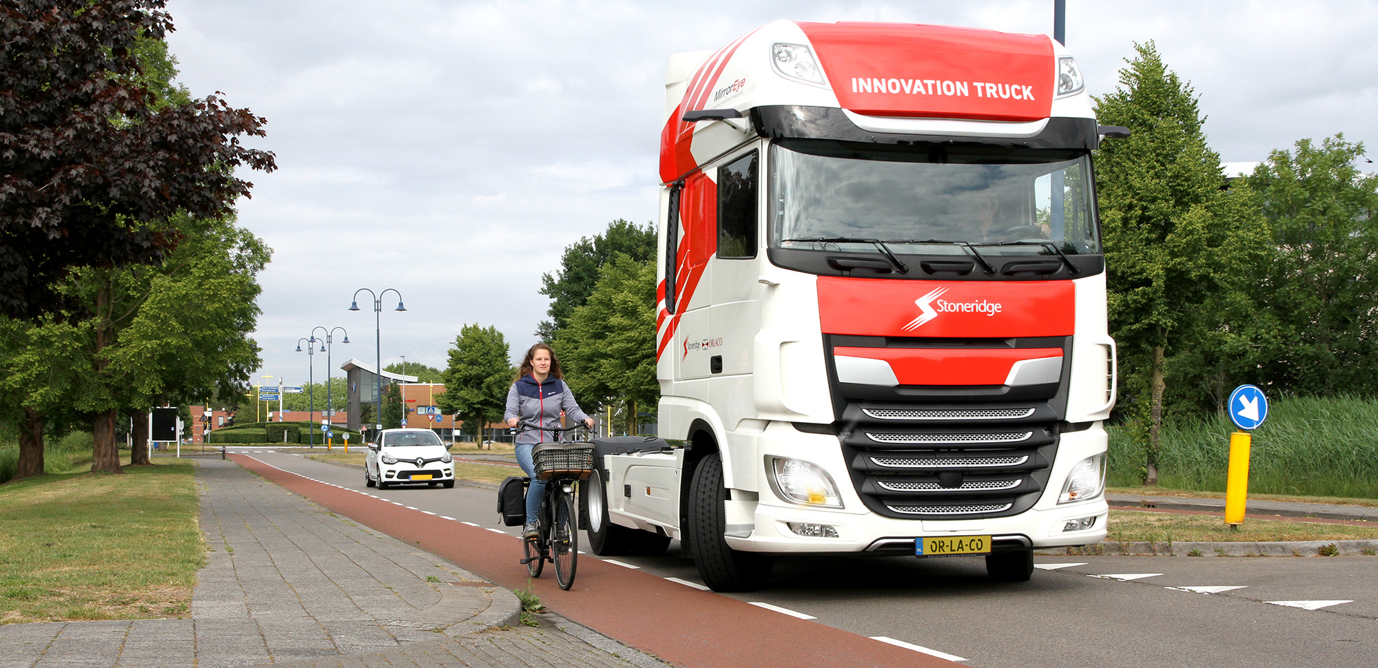 A large red and white Stoneridge 'innovation truck' driving down the road. There is a woman cycling in the bike lane beside the truck. On either side of the road there are trees and behind the truck on the road there is a white car.