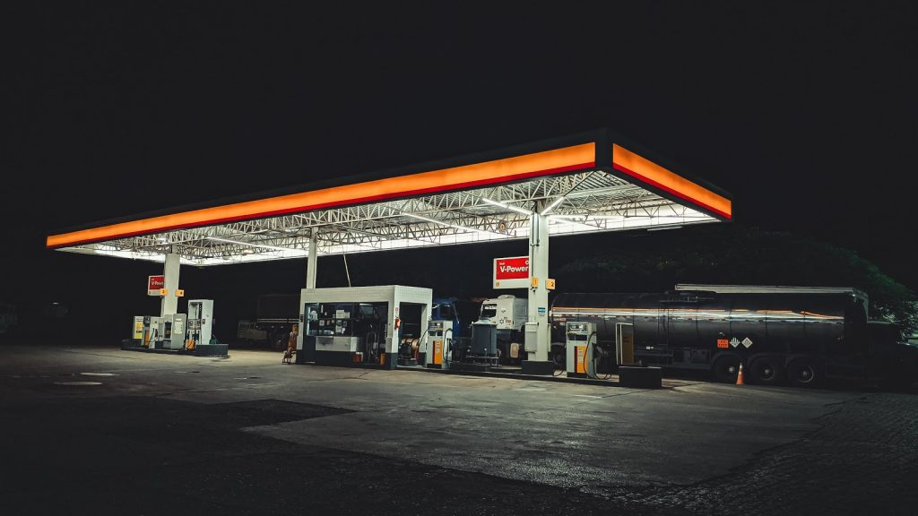 a truck driver at a petrol station during the night