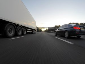 image of car and lorry on a motorway driving without a tachograph card in this situation would be unlawful