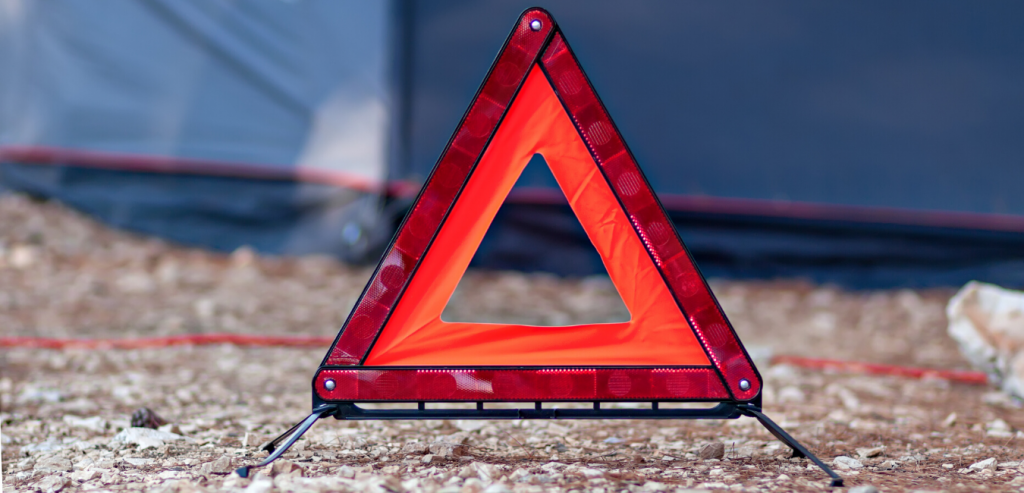 A reflective triangle set up on the side of the road. A reflective triangle is a must-have for long-haul trucking journeys