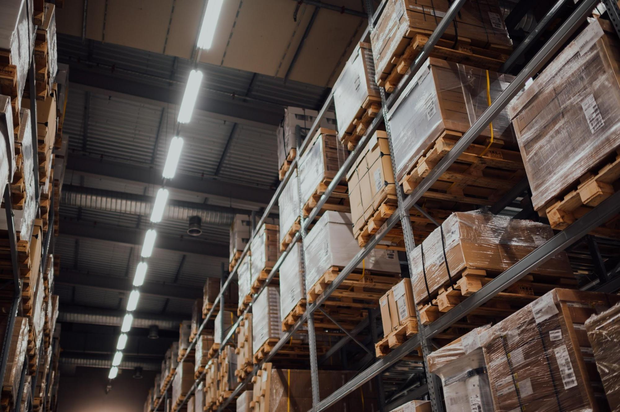 image showing the inside of a distribution warehouse which shows several pallets of products. Highlighting how COVID-19 has increased demand on logistics and driven digitalisation in the logistics sector