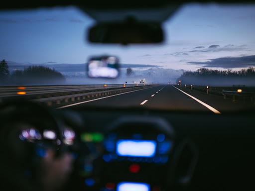 A person driving on the main road at night