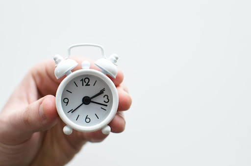 Someone holding a small white alarm clock