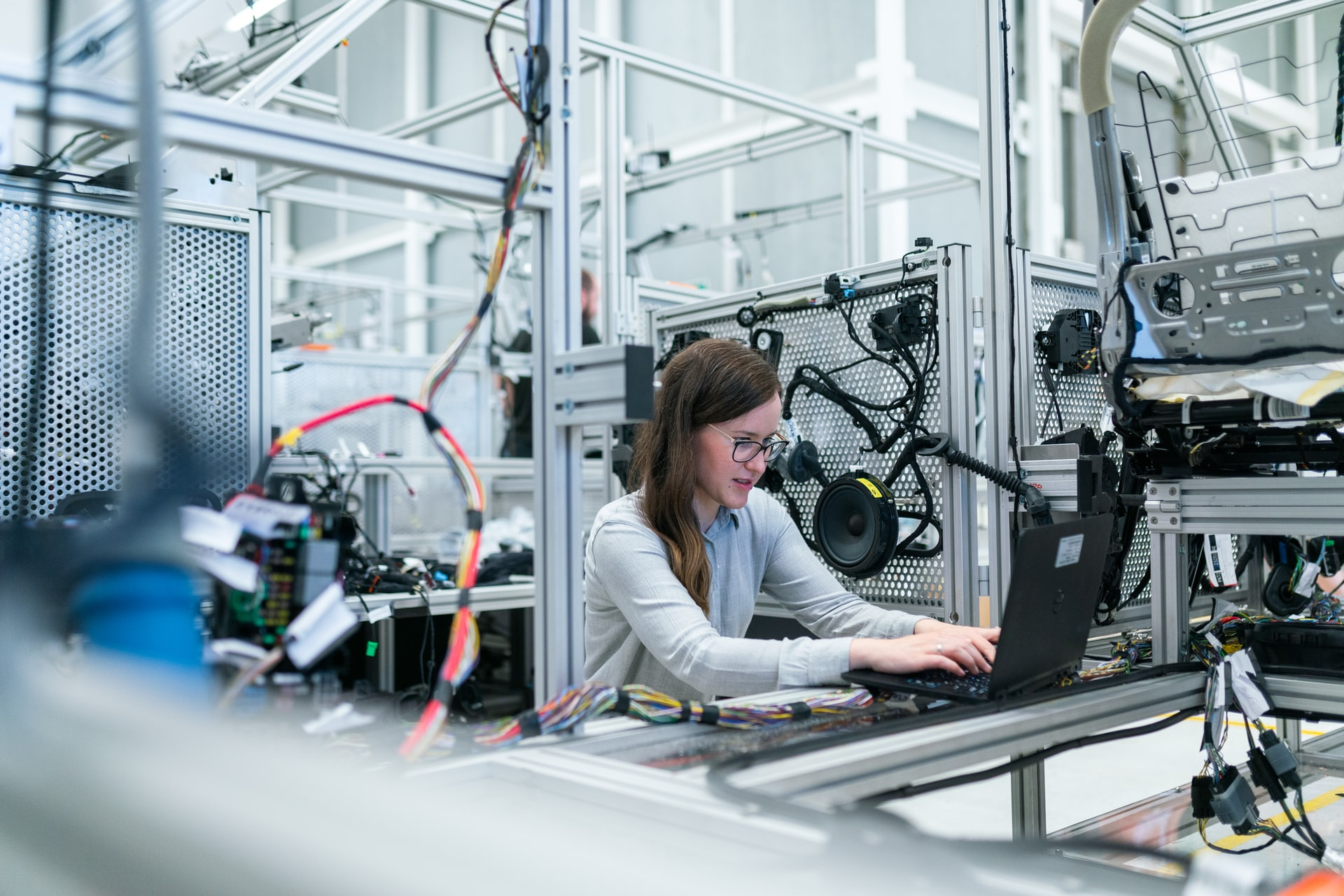 Woman on laptop quality testing in a factory for electronics and car parts. This is an important part of supply chain transparency for logistics